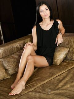 Привлекательная брюнетка стягивает трусы на диване - фото