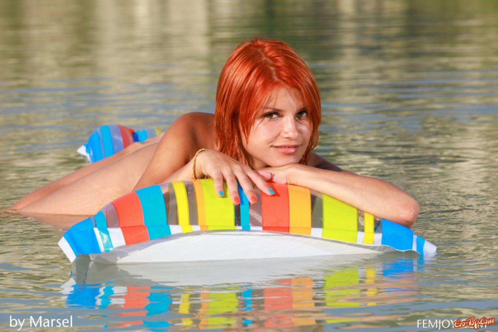 Голая рыжая девушка купается на надувном матраце.