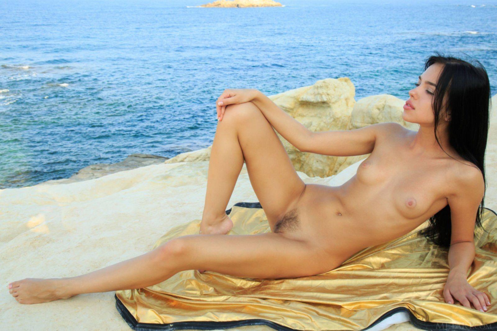 Брюнетка с волосиками на письке позирует голая у моря - фото