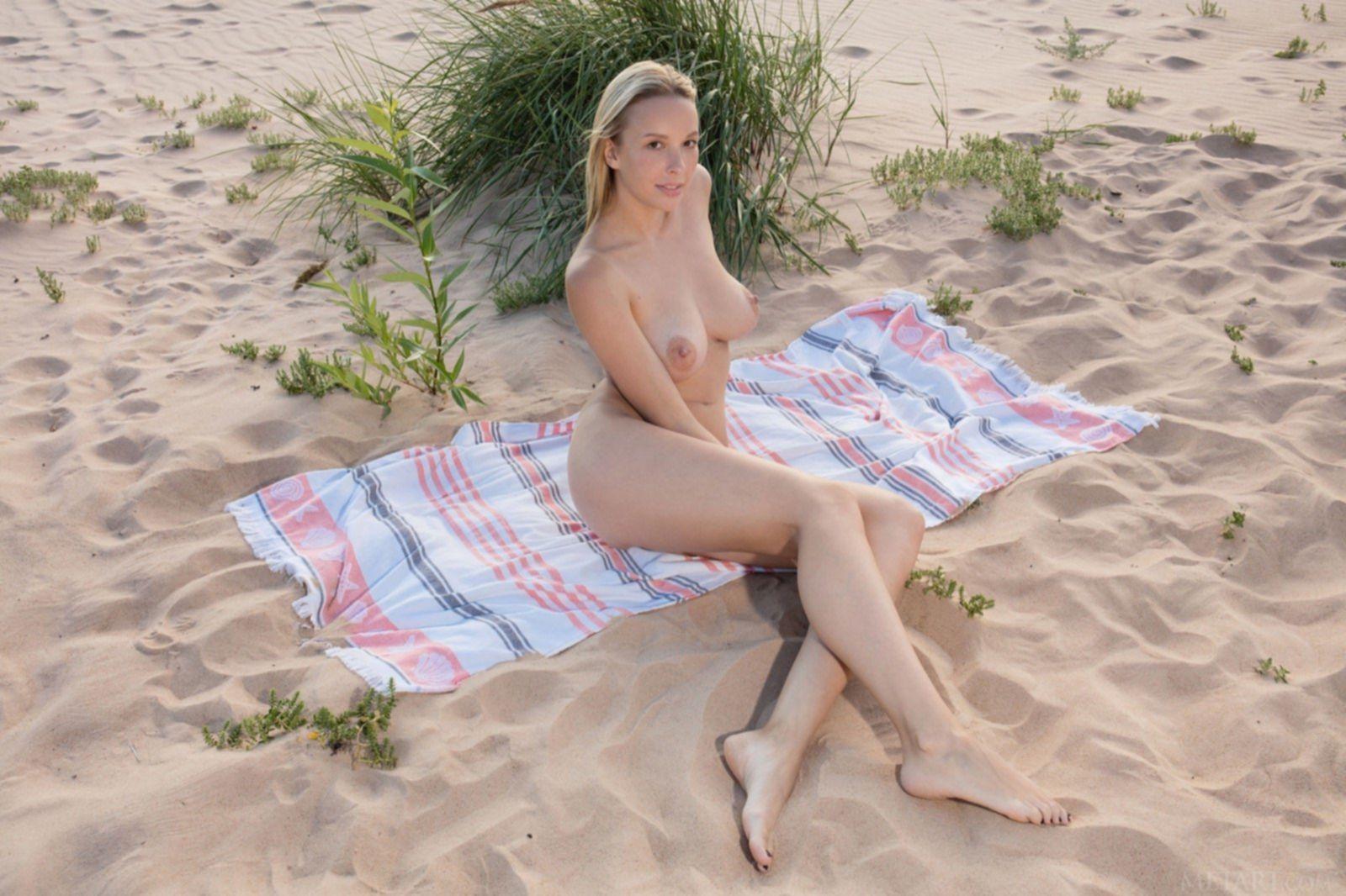 Красивая блондинка показывает сиськи на пляже - фото