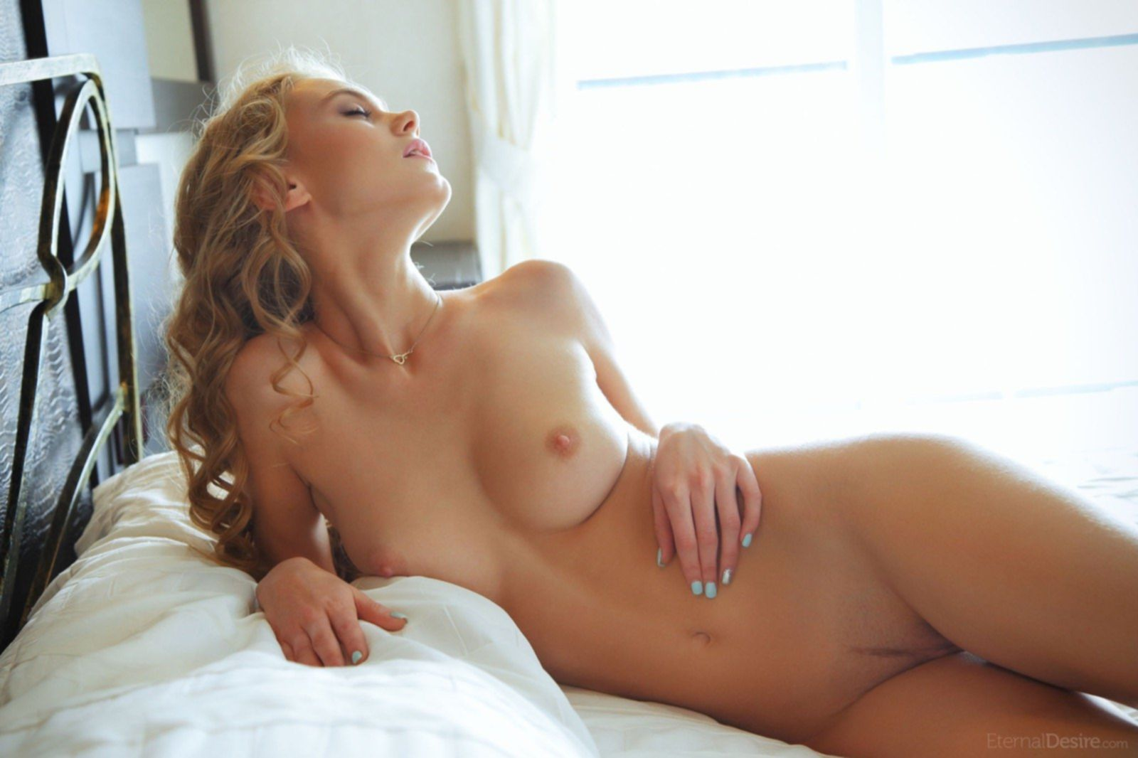 Девушка снимает пижаму на кровати - фото