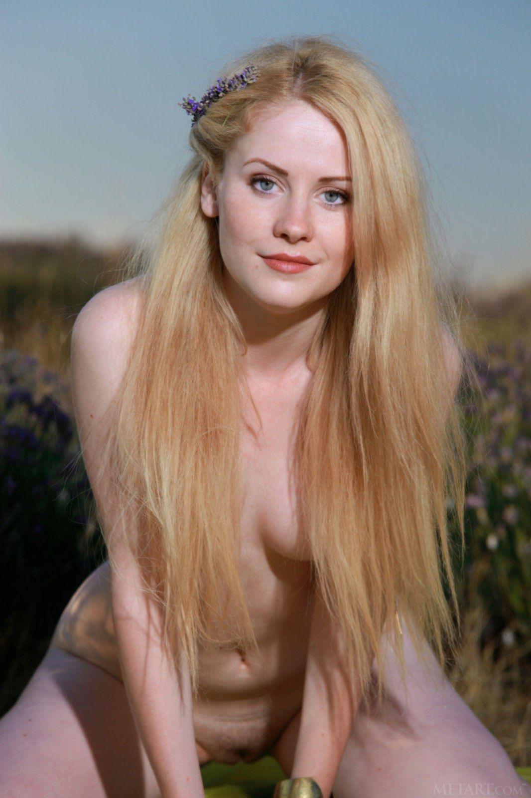 Красивая юная блондинка позирует голая на природе - фото