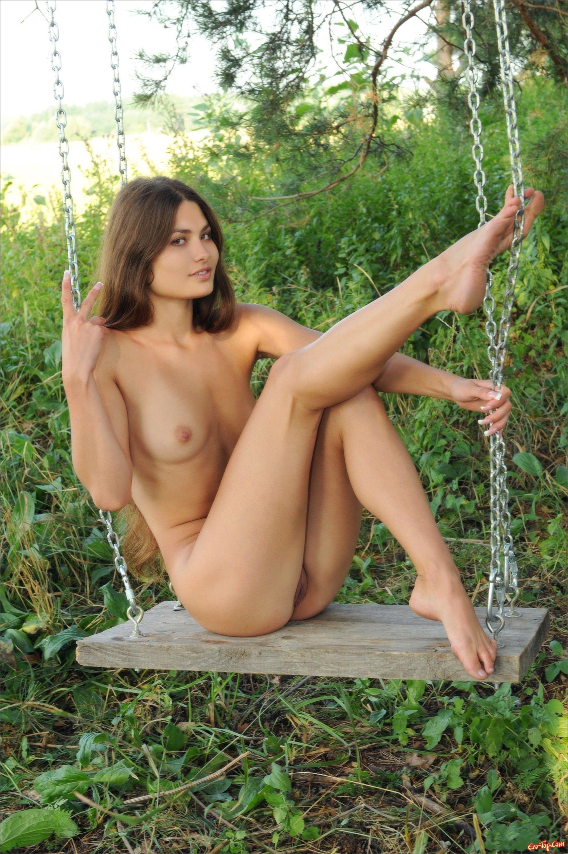 Голая девушка на качелях в лесу - фото эротика.