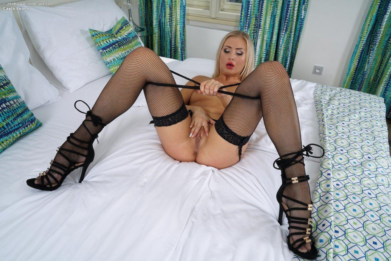 Сексуальная блондинка в чулках позирует в спальне - фото