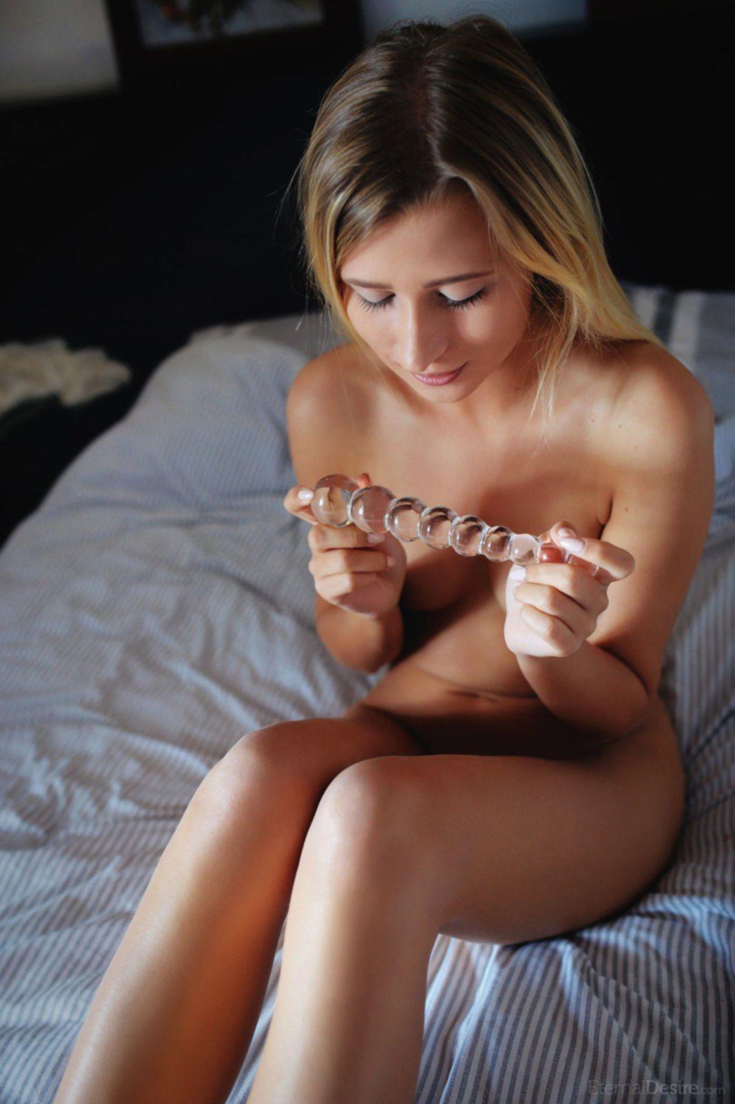 Развратная голая девушка развлекается на кровати - фото