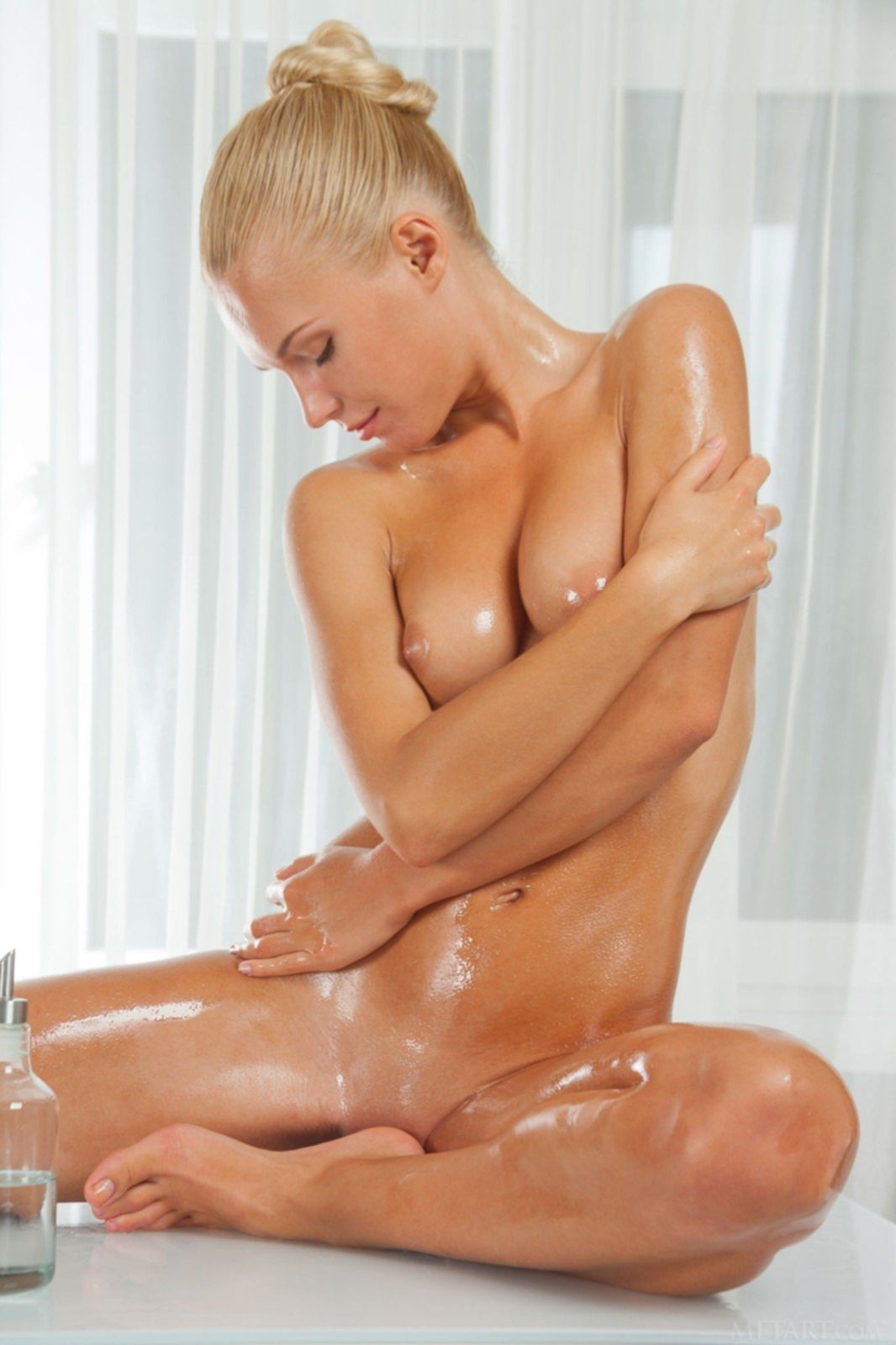 Красивая блондинка намазала сиськи и жопу маслом - фото