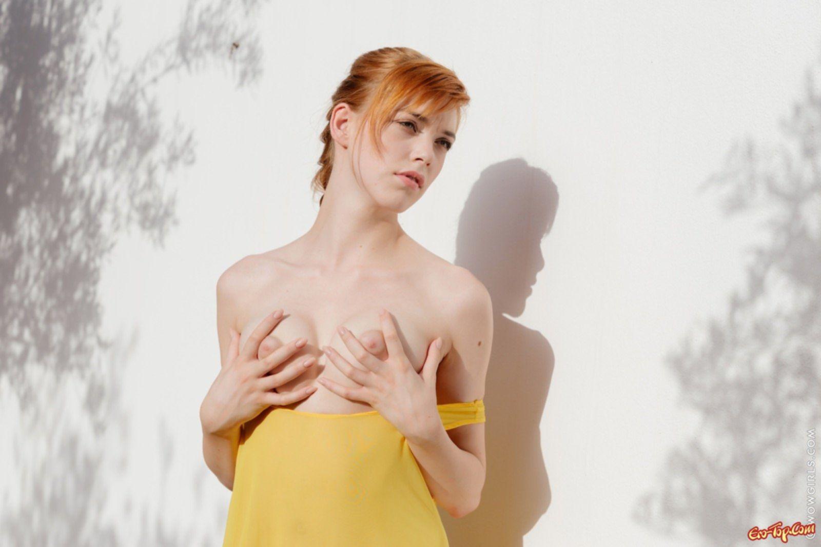Рыженькая милая девушка сняла платье стоя у стены - фото