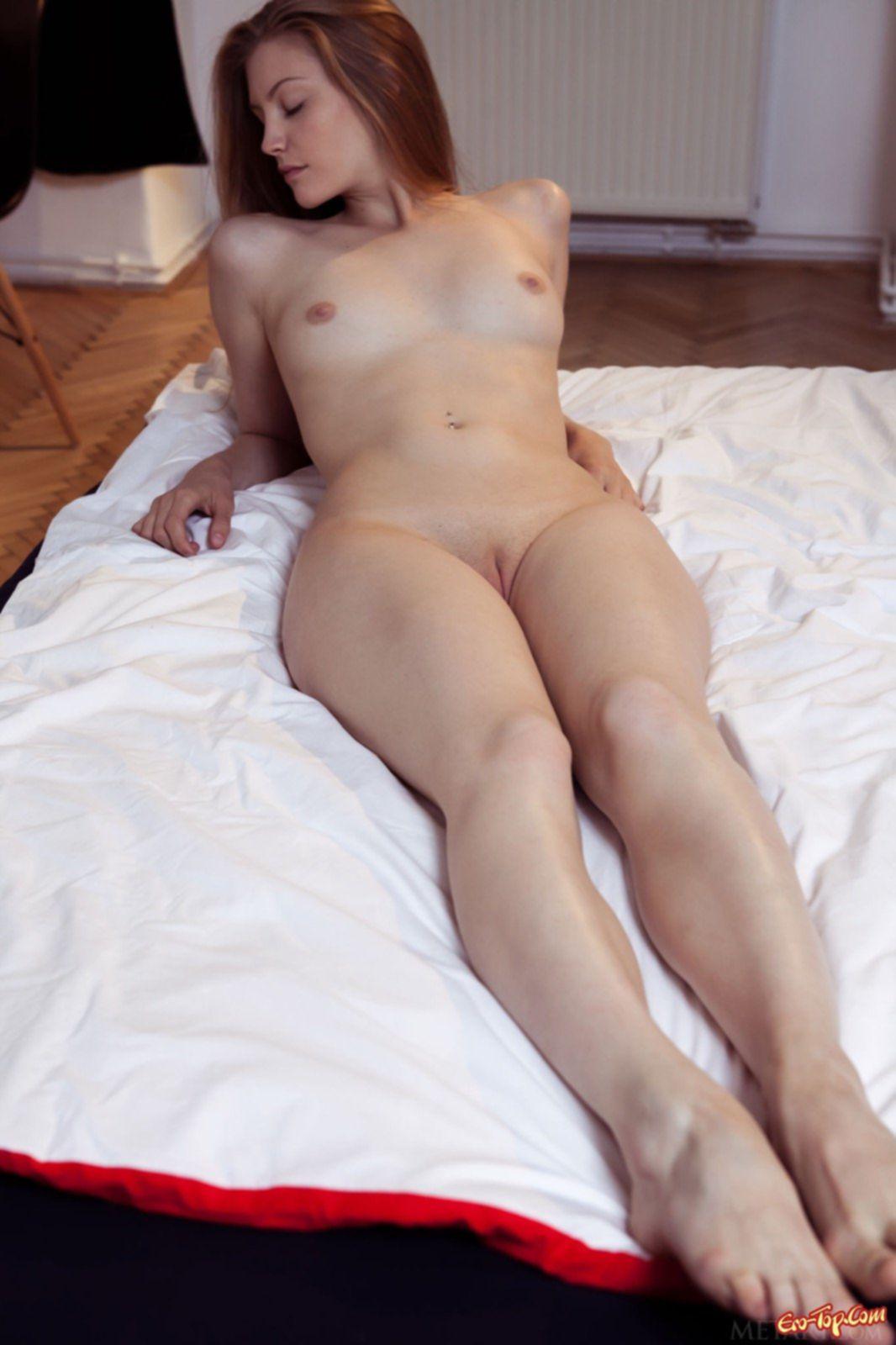 Рыжая девушка с упругой попкой позирует в постели - фото