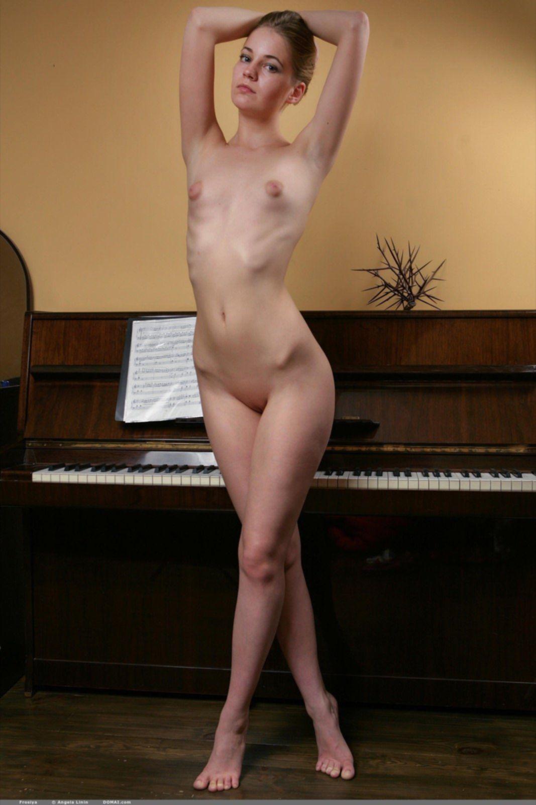 Голая девица в чулках позирует рядом с пианино - фото