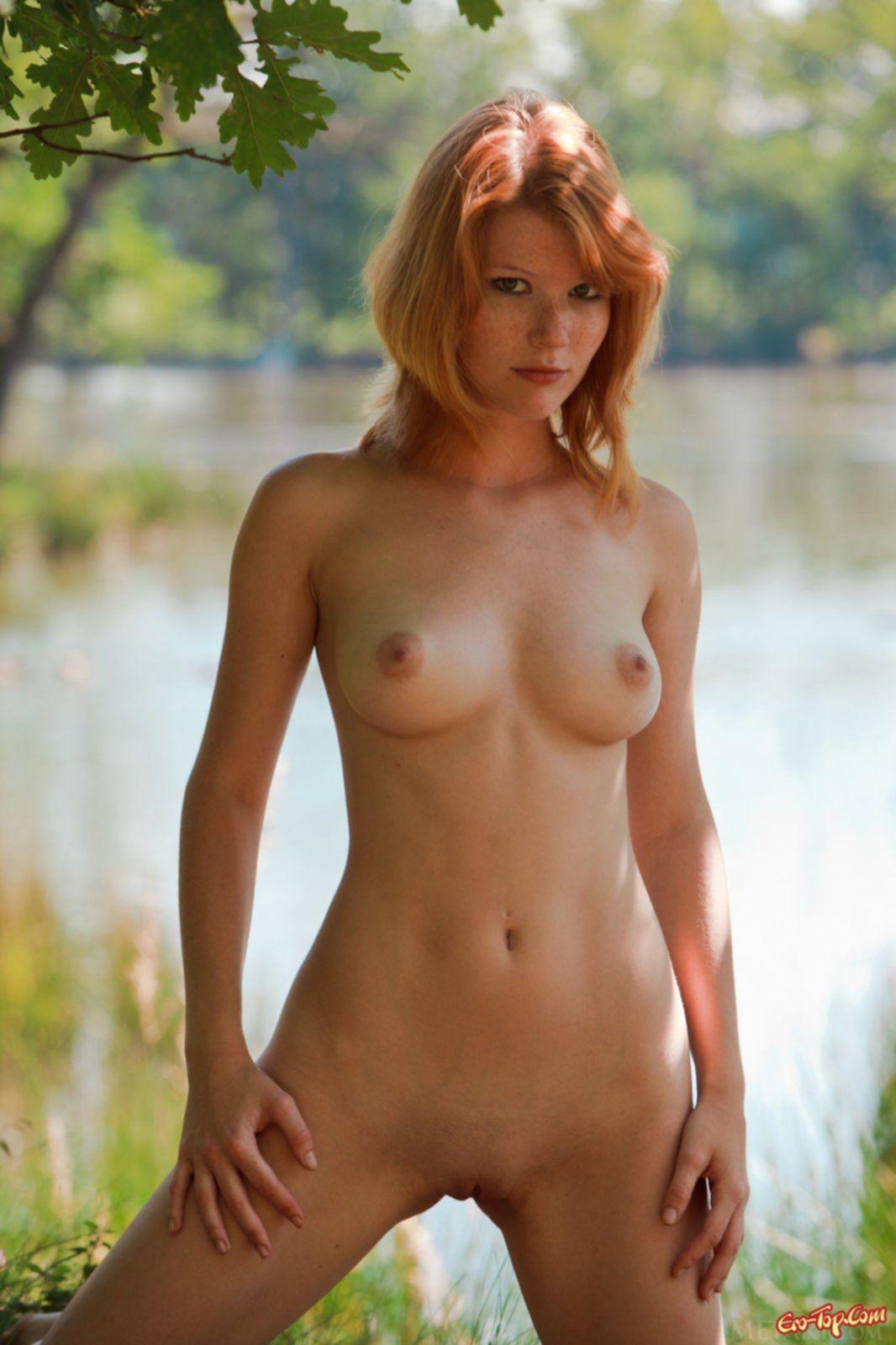 Рыжая баба хвастается сексуальным телом у озера - фото